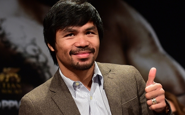 "(FILES) In this September 3, 2014 file photo, Filipino boxing star Manny Pacquiao gestures on arrival for a press conference with fellow boxer Chris Algieri in Los Angeles, California. Pacquiao called his boxing showdown with Floyd Mayweather ""the fight of my life"" as he got down to work pounding the streets and gym in Los Angeles. The eight-division world champion cranked into serious preparations for the May 2 fight after flying in for his training camp from his native Philippines. On March 2, 2015, Pacquiao ran two miles (3.2 km) and shadow-boxed for two rounds, followed by abdominal work and breakfast of steamed rice, scrambled egg, fish and chicken broth. AFP PHOTO / FREDERIC J. BROWN / FILESFREDERIC J. BROWN/AFP/Getty Images"